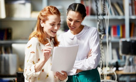 two business women looking at paper smiling